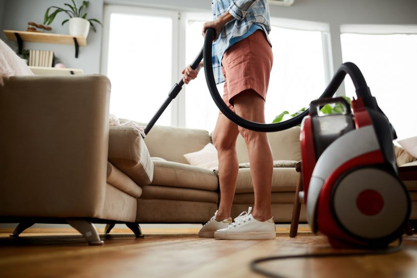 Cleaning sofa with vacuum cleaner