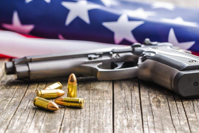 Pistol bullets, handgun and USA flag.